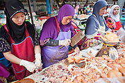 "Sept 25, 2009 -- PATTANI, THAILAND: Muslim women butcher chickens for customers in the morning market in Pattani, Thailand. Thailand's three southern most provinces; Yala, Pattani and Narathiwat are often called ""restive"" and a decades long Muslim insurgency has gained traction recently. Nearly 4,000 people have been killed since 2004. The three southern provinces are under emergency control and there are more than 60,000 Thai military, police and paramilitary militia forces trying to keep the peace battling insurgents who favor car bombs and assassination.  Photo by Jack Kurtz"