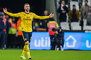 Calum Chambers (Arsenal) walking forward with his arms raised during the Premier League match between West Ham United and Arsenal at the London Stadium, London, England on 9 December 2019.