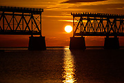 Setting Sun framed by historic and derelict old rail road bridge at Bahia Honda State Park the Florida Keys