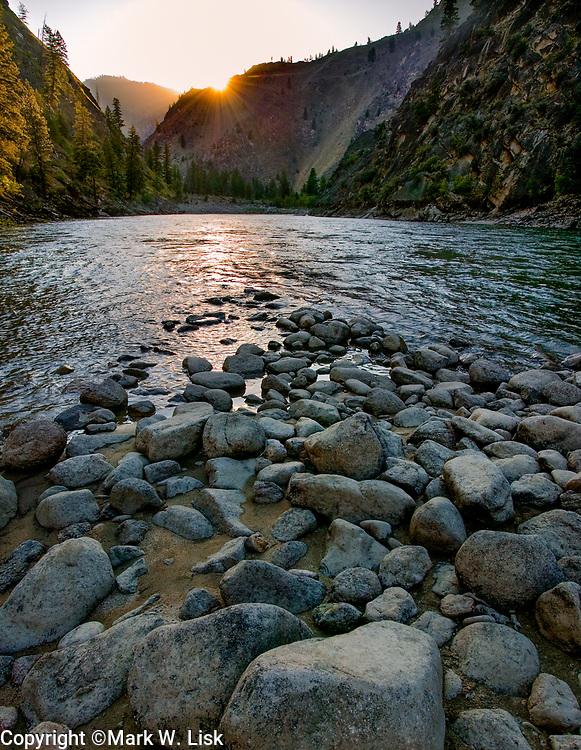 The sun sets behind the canyon rim on the Salmon River near Mann Creek camp.
