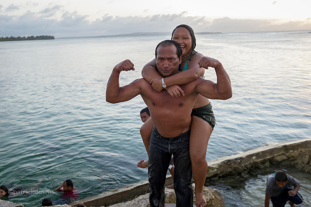 "A ""muscleman"" flexes after carrying a girl up from the water onto Sugar Dock during the lively hour. The beach and dock is a popular local swimming and party spot on the island."