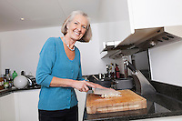 Portrait of happy senior woman chopping vegetables at kitchen counter