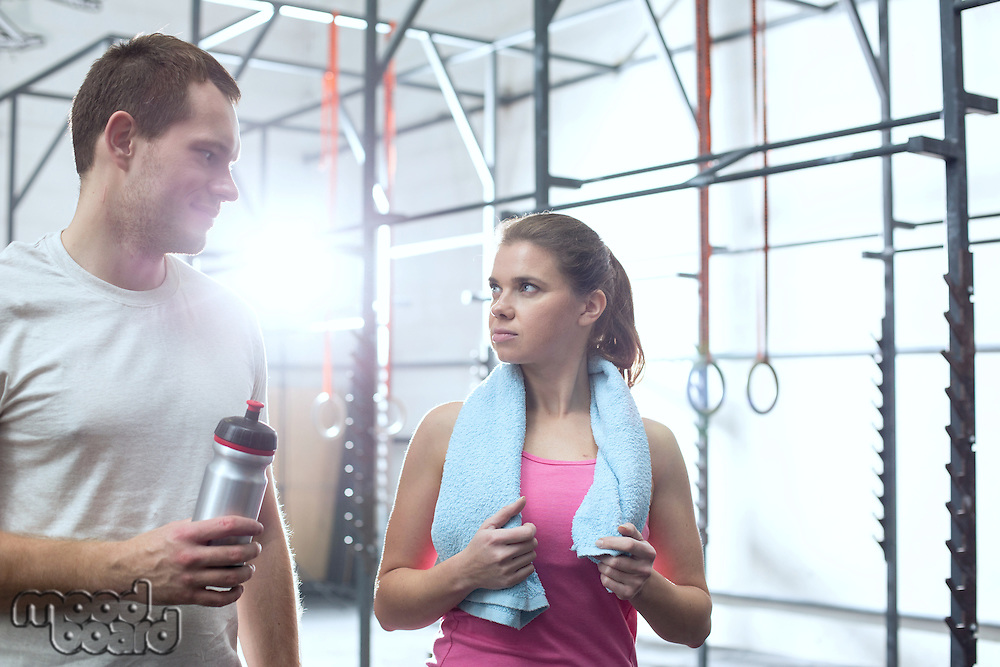 Man and woman looking at each other in crossfit gym
