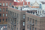 EAST HARLEM - MAR 13, 2014 - NYPD Officers and FDNY firefighters took up positions on nearby rooftops. Photo by Scott Klocksin/NYCity Photo Wire