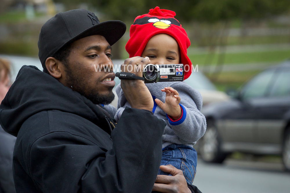 Middletown, New York - A man takes movies of the 60th annual Middletown Little League parade while holding a child on April 14, 2013.