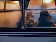 Junge hinter einer Autobus Glasscheibe in Jakutsk. Jakutsk hat 236.000 Einwohner (2005) und ist Hauptstadt der Teilrepublik Sacha (auch Jakutien genannt) im Foederationskreis Russisch-Fernost und liegt am Fluss Lena. Jakutsk ist im Winter eine der kaeltesten Grossstaedte weltweit mit durchschnittlichen Winter Temperaturen von -40.9 Grad Celsius. Die Stadt ist nicht weit entfernt von Oimjakon, dem Kaeltepol der bewohnten Gebiete der Erde.<br /> <br /> Boy sitting behind a window of a Yakutsk bus. Yakutsk is a city in the Russian Far East, located about 4 degrees (450 km) below the Arctic Circle. It is the capital of the Sakha (Yakutia) Republic (formerly the Yakut Autonomous Soviet Socialist Republic), Russia and a major port on the Lena River. Yakutsk is one of the coldest cities on earth, with winter temperatures averaging -40.9 degrees Celsius.