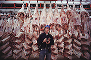Photographer Peter Menzel in front of cooling beef carcass parts. The Harris Ranch slaughterhouse, the Harris Beef Company, in Selma, California kills more than 700 head of cattle a day. Beef carcasses are cooled in a huge refrigerated room. San Joaquin Valley, California. USA .[[From the company: THE HARRIS FARMS GROUP OF COMPANIES. Harris Farms, Inc. is one of the nation's largest, vertically integrated family owned agribusinesses]].