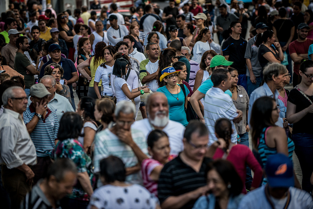 CARACAS, VENEZUELA - JULY 16, 2017: Thousands of people wait in line to vote in Caracas. Today, at over 2,000 polling locations, Venezuelans participated in a symbolic vote, called by the political opposition to the Socialist government. Ballots had three questions: ONE - Do you refuse the government's plans for a new constituent assembly, without prior approval from the people, TWO - Do you demand that government employees obey and defend the 1999 Constitution and respect the decisions of the National Assembly, and THREE - Do you approve that powers should be established by the Constitution, and that we should have free and transparent elections? The opposition held this vote, as a massive act of civil disobedience to show that the people disapprove of the government. For over 3 months, anti-government protests have raged across Venezuela.  PHOTO: Meridith Kohut