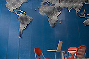 Laptop on table in empty office with world map on wall