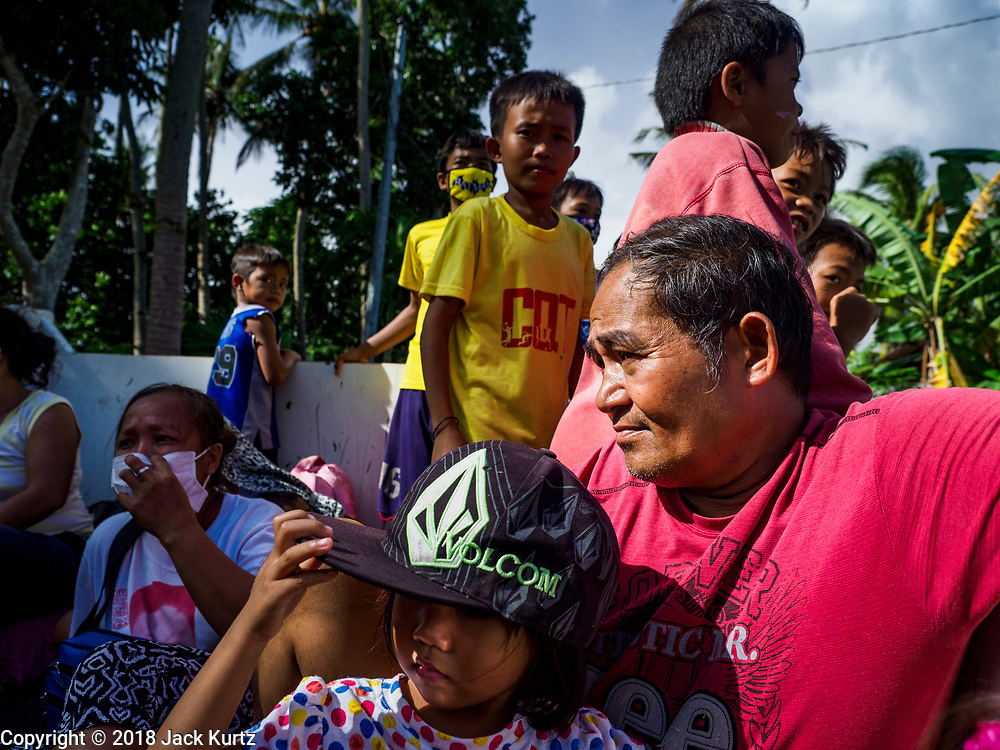 "22 JANUARY 2018 - CAMALIG, ALBAY, PHILIPPINES: People evacuated from their homes on the slopes of the Mayon volcano ride in a government truck to an evacuation center. There were a series of eruptions on the Mayon volcano near Legazpi Monday. The eruptions started Sunday night and continued through the day. At about midday the volcano sent a plume of ash and smoke towering over Camalig, the largest municipality near the volcano. The Philippine Institute of Volcanology and Seismology (PHIVOLCS) extended the six kilometer danger zone to eight kilometers and raised the alert level from three to four. This is the first time the alert level has been at four since 2009. A level four alert means a ""Hazardous Eruption is Imminent"" and there is ""intense unrest"" in the volcano. The Mayon volcano is the most active volcano in the Philippines. Sunday and Monday's eruptions caused ash falls in several communities but there were no known injuries.    PHOTO BY JACK KURTZ"