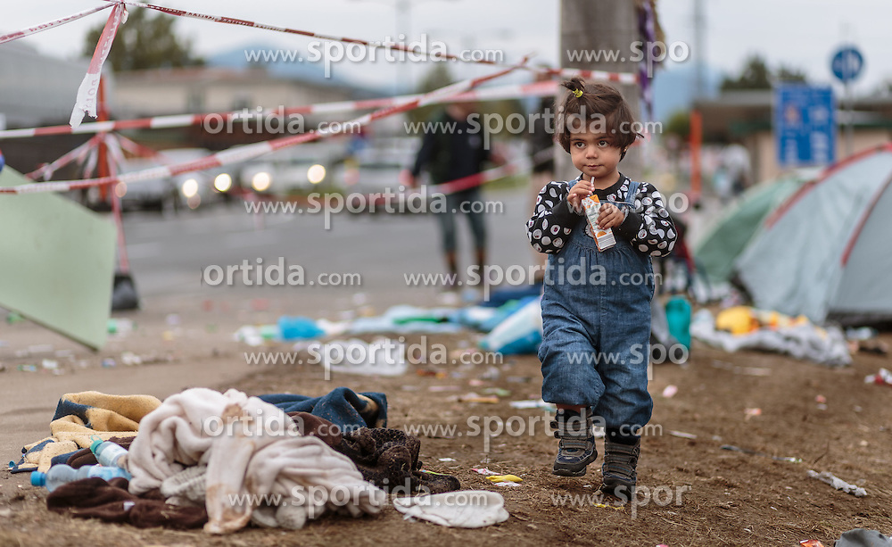 25.09.2015, Grenzübergang, Salzburg, AUT, Fluechtlingskrise in der EU, im Bild Flüchtlinge an der Grenze zu Deutschland, ein Mädchen spaziert durch Müll // Migrants on the German Border, a girl walking through garbage. Thousands of refugees fleeing violence and persecution in their own countries continue to make their way toward the EU, border crossing, Salzburg, Austria on 2015/09/25. EXPA Pictures © 2015, PhotoCredit: EXPA/ JFK
