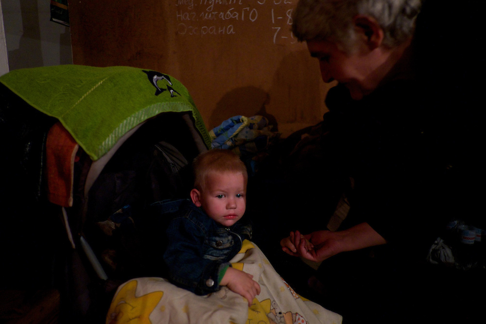 DONETSK, UKRAINE - OCTOBER 16, 2014: A local IDP comforts a child at a Soviet era bomb shelter in Petrovskiy district, Donetsk. The daily routine of the almost hundred people living here for the past four months, can be tedious as the regular shellfire between DNR rebels and the Ukrainian National Guard is a constant threat that constrain them to stay underground most of the time. CREDIT: Paulo Nunes dos Santos