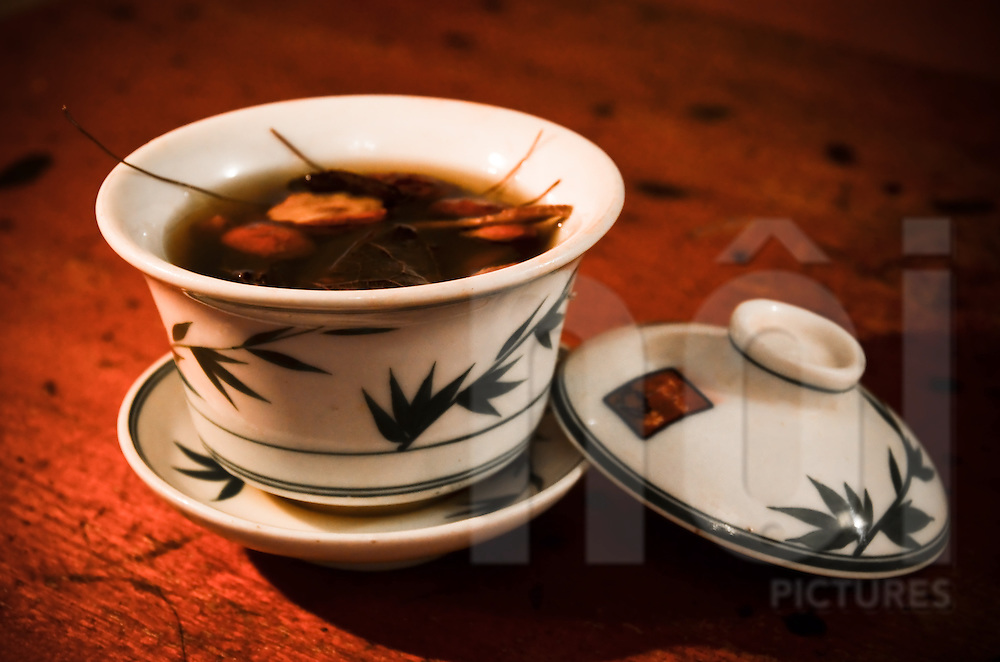 Cup of fruity tea sitting on a wooden table, Hanoi, Vietnam, Southeast Asia