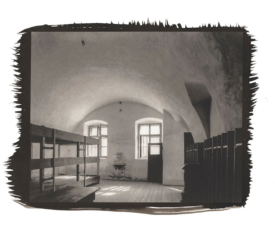 A barracks room with wooden bunks on one side and lockers on the other is illuminated by light from a window.