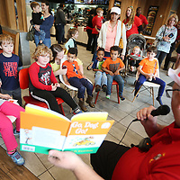 "Capitan Mark Patton, with the Tupelo Fire Department, Station 6, reads ""Go. Dog. Go!"" by Dr Seuss to area children at McDonald's on West Main Street in Tupelo Thursday night as part of Dr. Seuss week."
