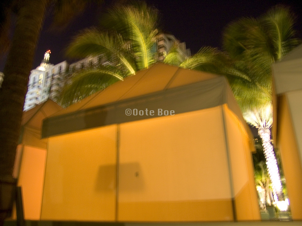 close up of tent with palm trees and hotel in the background Miami Beach