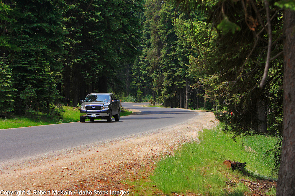 IDAHO. Cascade Lake. Vehicles rounding corner on forest road in summer. #cr080037