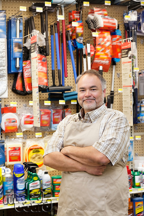 Portrait of a confident mature salesperson with arms crossed in hardware store