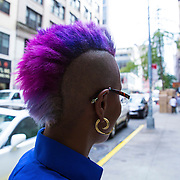 A fashionable lady with a purple and blue mohawk haircut is seen on the street in New York City on Monday, September 28, 2015.  (Alex Menendez via AP)