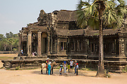 Tourists stand  and pose for photographs outside The Outer Gallery, Angkor Wat, Krong Siem Reap, Cambodia. Angkor Wat is a temple complex in Cambodia and the largest religious monument in the world, with the site measuring 162.6 hectares. It is Cambodia's main tourist destination.  (photo by Andrew Aitchison / In pictures via Getty Images)