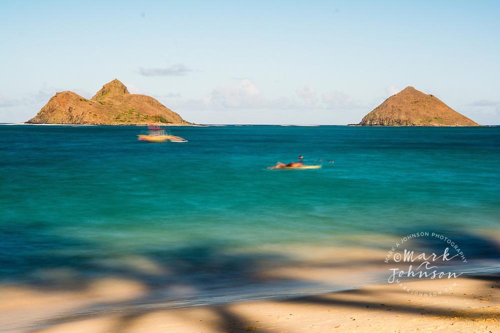 Long exposure photograph of palm tree shadows on Lanikai Beach, the Mokulua Islands offshore, Kailua, Oahu, Hawaii