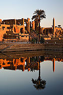 Karnak Temple and the Sacred Lake at sunrise. Karnak was the residence of gods, Amon-Re, his wife Mut, and their son Khonsu, the moon god. The Temple of Karnak is located 4 kilometers north of modern day Luxor, or ancient Thebes.  Built in the 12th dynasty, 2000 B.C.- 220 B.C.