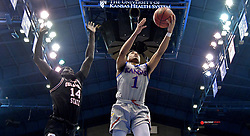 Feb 24, 2020; Lawrence, Kansas, USA;Kansas Jayhawks guard Devon Dotson (1) shoots as Oklahoma State Cowboys forward Yor Anei (14) defends during the first half at Allen Fieldhouse. Mandatory Credit: Denny Medley-USA TODAY Sports
