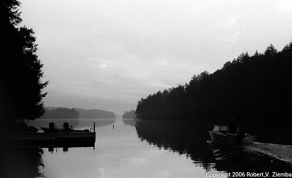 A black and white image of a small boat heading out on the lake passing a dock