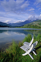 Two white chairs sit by Green Lake in Whistler on a summer day, with the mountains dusted in snow and reflected in the lake.