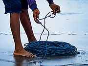 29 JULY 2017 - AIRKUNING, BALI, INDONESIA: A fisherman in Airkuning, a Muslim fishing village on the southwest corner of Bali, coils the rope as villagers haul in a fishing net that had been laid by outrigger canoes from the village. Villagers said their regular catch of fish has been diminishing for several years, and that are some mornings that they come back to shore with having caught any fish.    PHOTO BY JACK KURTZ