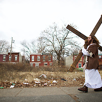 """Michael Grant, 28, """"Philly Jesus,"""" carries a 12 foot cross 8 miles through this blighted area of North Philadelphia towards LOVE Park in Center City as part of a Christmas walk to spread the true message of the holiday in Philadelphia, PA on December 20, 2014.   As many as a half dozen others joined him for numerous miles as he trekked southward down Broad Street.  Some shouted """"Praise Jesus!"""" and """"Thank you for doing this!""""at the sight.  Nearly everyday for the last 8 months, Grant has dressed as Jesus Christ, and walked the streets of Philadelphia to share the Christian gospel by example.  He quickly acquired the nickname of """"Philly Jesus,"""" which he has gone by ever since. REUTERS/Mark Makela (UNITED STATES)"""