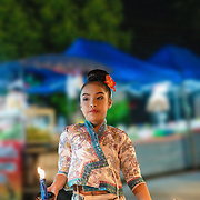 Young Thai girl performing traditional dance at a night market in Chiang Mai