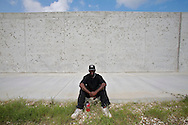 Ward Dell Hunter sits in front of the new Industrial canal levee. His was a resident of New Orleans east and lost his wife 4 days after Katrina to stress and a heart attack. he spent 4 days on the roof of his house before getting rescued..Citizens of the 9th Ward of New Orleans marched over the two bridges over the industrial canal to commemorate the Hurricane Katrina disaster one year ago today..Residents of the Lower 9th threw flowers into the canal and then marched into Downtown New Orleans..