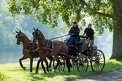 © Licensed to London News Pictures. 15/05/2014. Windsor, UK. Riders drive their carriage along the River Thames in the early morning sunshine. The second day of The Royal Windsor Horse Show, set in the grounds of Windsor Castle. Established in 1943. Photo credit : Stephen Simpson/LNP