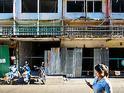 29 JUNE 2015 - BANGKOK, THAILAND: People go past an old shophouse on Sukhumvit Soi 95. The shophouse, which is next to the Bang Chak Market, is being torn down to make way for a new development. The Bang Chak Market serves the community around Sois 91-97 on Sukhumvit Road in the Bangkok suburbs. About half of the market has been torn down, vendors in the remaining part of the market said they expect to be evicted by the end of the year. The old market, and many of the small working class shophouses and apartments near the market are being being torn down. People who live in the area said condominiums are being built on the land.     PHOTO BY JACK KURTZ