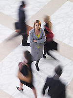 Business woman standing amongst people walking elevated view long exposure