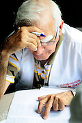 Cuban Dr. Miguel Almaguer scrutinising the results of medical test data, as part of a series of medical investigations carried out by the 'Nefrolempa' health team into the high incidence of chronic renal failure in the region.<br /> <br /> Ciudad Romero, Bajo Lempa, El Salvador. 2011.<br /> The 'Nefrolempa' research project is a collaboration between the El Salvador Ministry of Health, the Nephrology Institute of Cuba's Ministry for Public Health and the United Bajo Lempa Committee Association. The aim of the project is to investigate the reasons for the high levels of Chronic Kidney Disease (CKD) suffered by the communities within the Bajo Lempa region. It is exploring whether the use of agrochemicals might be a factor in the prevalence of the disease.<br /> <br /> Medical team: Dr Elsy Brizuela de Jimenez, Directora Unidad de Salud. Miriam Colindres, Nurse. Maria Eraida Velasquez, clinic and laboratory worker. Ecuilia Castro Peraza, Nutritionist. Veronica Contreras, Education for health. Guadelupe Nunez, Psychologist. Luis Diaz General support worker. Dr Raul Herrera Valdes, Nefrologo, Cuba. Dr Miguel Almaguer Lopez, Nefrologo Cuba. Dr Carlos Orantes, Salvadorean Nefrologist. Dr Juan Carlos Awaya, Salvadorean Nefrologist.