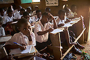 Esperance Mulwefakadi, ten years old takes notes during a 6th year class at the Bana Kimono primary school, Kikwit, Bandundu Province, Democratic Republic of Congo on November 14, 2014. Esperance received a scholarship through the program &lsquo;VAS-Y Fille&rsquo; and has been able to continue the last two years of school. From a disadvantaged family, her mother has been sick and bed ridden for many years and her father and extended family whom she lives with scrape by collecting manyok roots which they dry and sell to make a meagre living. &ldquo;I would like to continue my studies into high school if my family has the means to support me and I dream of one day becoming a nurse.&rdquo;<br /> The Bana Kimono primary school has 394 students with 40 in total female students receiving a scholarship from years 5 &amp; 6. CRS with partner Caritas and organisations International Rescue Committee and Save the Children are engaged in a education initiative focusing on assisting female students from financially disadvantaged families continuing studies in the final two years of primary school. The program 'VAS-Y Fille&rsquo; or &lsquo;Go Girl!&rsquo; supplies scholarships to help pay the school fees and books for students from disadvantaged families.