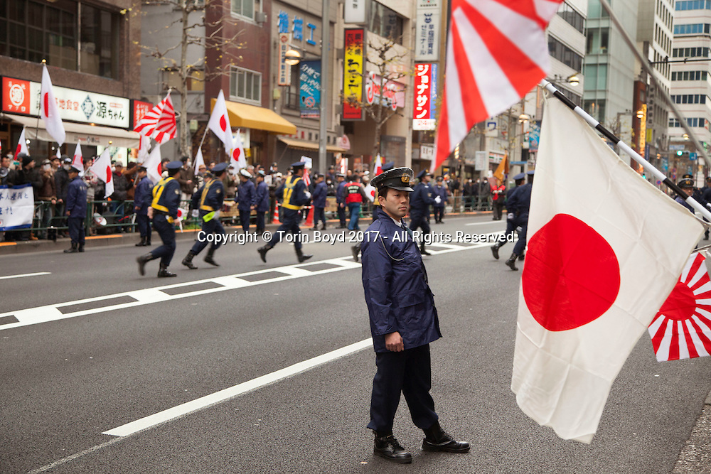 """February 5, 2017, Tokyo, Japan: Tokyo Metropolitan police officers cordoned off the entrance to APA Hotel's Shinjuku Gyoenmae branch during a demonstration by ultra-right wingers angered by APA's planned removal of a controversial history revisionist book from hotel rooms hosting athletes of the 2017 Sapporo Asian Winter Games. The book in question written by Toshio Motoya, the hotel chain's Chief Executive, claims the 1937 Nanjing Massacre was a fabrication. Writing under the pen name Seiji Fuji, Motoya's book entitled """"Theoretical Modern History II"""" is placed in every APA Hotel room in Japan and sold at their reception desks. The Tokyo based APA Hotel group is one of the largest hotel chains in Japan with over 400 hotels across the country. In the past 2-3 years APA has benefitted from a tourism boom to Japan in which 40% of their guests are foreign visitors and half that amount are Chinese and Korean nationals. As a result, China and Korea have been outraged by APA and a large boycott began in late January by both countries. This led to APA announcing they would pull Motoya's books from athlete's rooms only during the Asian Winter Games, infuriating Japanese right wingers. The demonstrators at this event are part of a group who call themselves """"Group of Warriors Protecting the Nation"""" (Gokoku Shishi no Kai). Photo by Torin Boyd."""