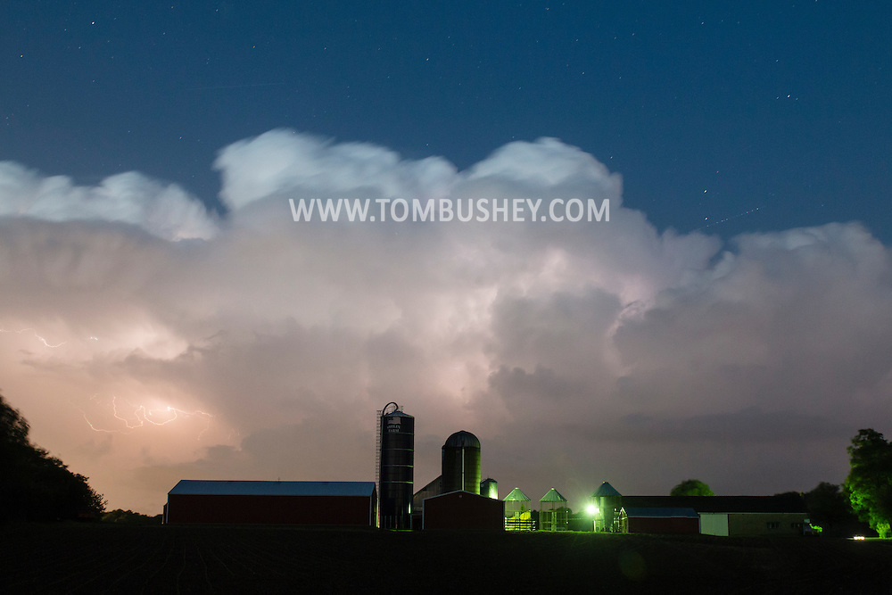 Lightning flashes in the clouds above the barn and silos at Smiley Farm in the Town of Wallkill, New York, during a spring thunderstorm.