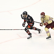 Matt Benning #5 of the Northeastern Huskies and Patrick Brown #23 of the Boston College Eagles skate to the puck during The Beanpot Championship Game at TD Garden on February 10, 2014 in Boston, Massachusetts. (Photo by Elan Kawesch)