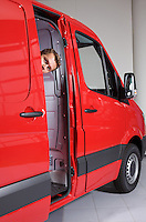 Young man peeking through van door