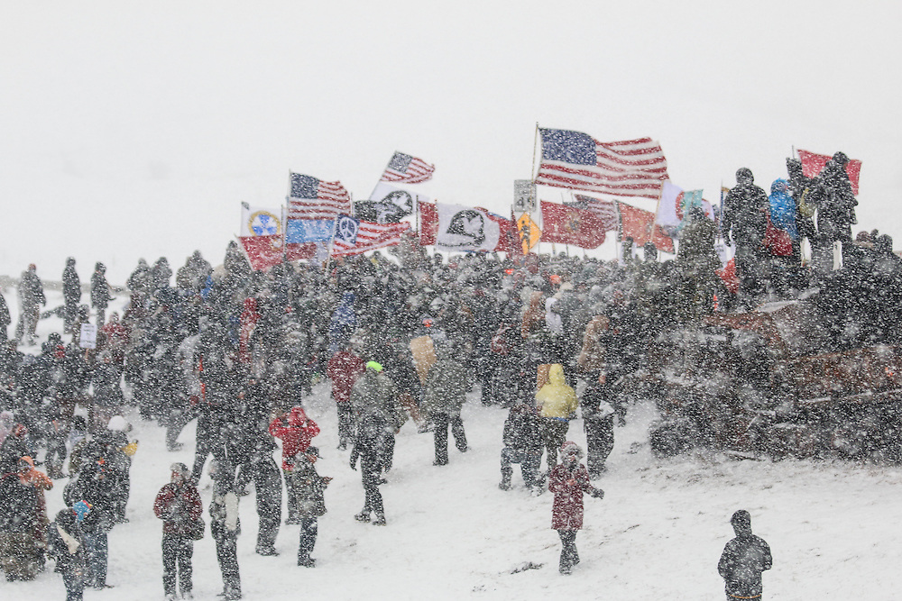 Protestors gather in prayer after marching toward barricades on the Backwater Bridge on Highway 1806 with support from US military veterans on Army Corps of Engineers land bordering the Standing Rock Indian Reservation in Cannon Ball, North Dakota in December 2016.<br />