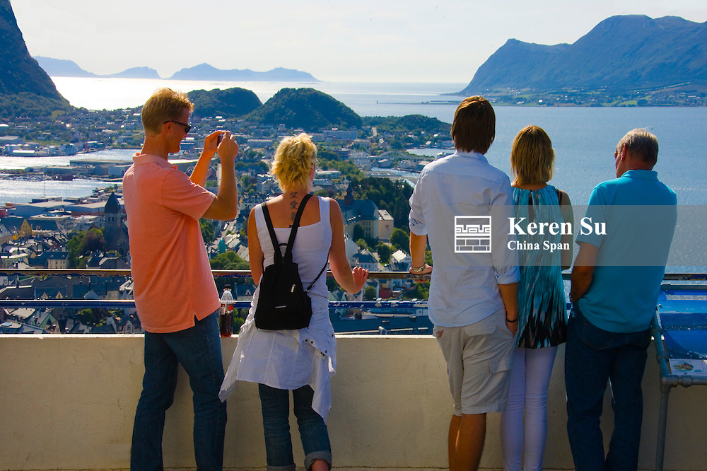 Tourists watch cityscape of Alesund, Norway