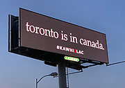 """General overall view of billboard promoting the recruitment Toronto Raptors free agent forward Kawhi Leonard to sign with the LA Clippers along the Interstate 5 freeway, Monday, June 24, 2019, in the Los Angeles suburb of Downey, Calif. The advertisement with a black background reads in white letters """"toronto is in canada"""" with the hashtag #KAWHI2LAC."""