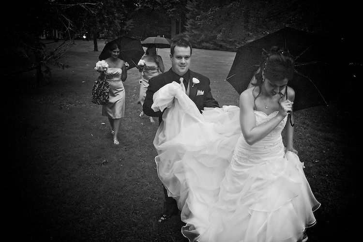 A damp and rainy afternoon on the grounds of the  Glenhyrst Art Gallery was the set for the bridal party wedding photography. Here, Brad holds Katies dress-trail as she hold her umbrella above her head to keep from getting wet. <br /> <br /> To view Katie and Brad's complete Wedding Gallery Collection, visit the Client Area and log-in. You'll be able to view all images as a slideshow, order prints and more.<br /> <br /> &copy; Images of a Promise by Dean Oros Photo + Design