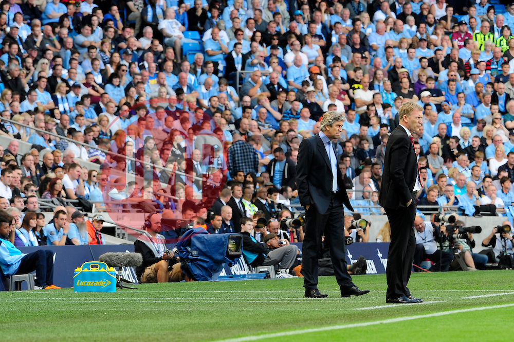 Manchester City Manager, Manuel Pellegrini and Manchester United Manager, David Moyes watch from the sideline - Photo mandatory by-line: Dougie Allward/JMP - Tel: Mobile: 07966 386802 22/09/2013 - SPORT - FOOTBALL - City of Manchester Stadium - Manchester - Manchester City V Manchester United - Barclays Premier League