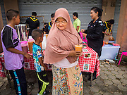 14 JUNE 2015 - NARATHIWAT, NARATHIWAT, THAILAND: A Muslim woman picks up a milk tea from Thai Army Rangers during a food distribution before Ramadan in Narathiwat. Ramadan starts June 18. The annual food distribution event is organized by the Southern Peace Media Club, a group of Thai journalists who work in the southern provinces of Pattani, Narathiwat and Yala. An insurgency pitting Muslim extremists against the Thai government has rocked Thailand's southern three provinces since 2001. More than 6,000 people have been killed in the sectarian violence.    PHOTO BY JACK KURTZ