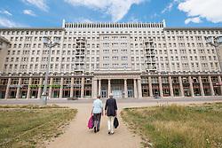Two women walking towards historic socialist former East German apartment buildings on Karl Marx Allee in Berlin Germany