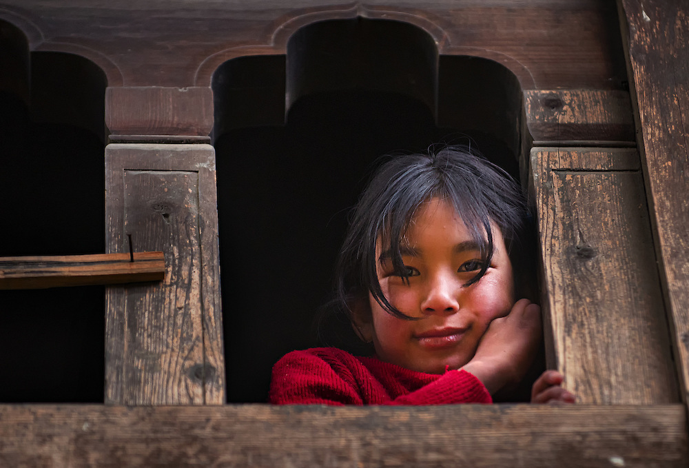 A girl looks out of her home in rural Bhutan.
